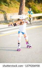 A little caucasian girl with roller quad rolling in the sun summer evening. The bicycle path of Koper, Slovenia
