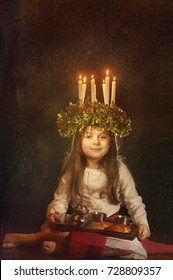 Little caucasian girl in Saint Lucia costume with crown of candles and lussekatter, a traditional swedish sweet. Copy space.