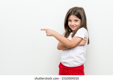 Little caucasian girl smiling cheerfully pointing with forefinger away.