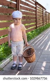 Little Caucasian girl standing with basket in inner yard in summer time