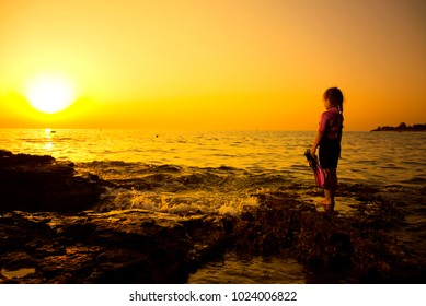 Little caucasian girlie on the rock, with sunset in background. Croatian cost, seaboard. Summer, travel, sport and recreation concept. Copy space.