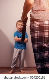 Little caucasian kid and mother with belt. Domestic violence, child abuse.