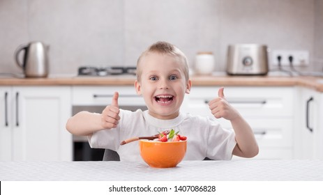 Little caucasian smiling boy sitting at the kitchen table and eat porridge with strawberry. Healthy breakfast before school and kindergarten at home. Thumbs up.