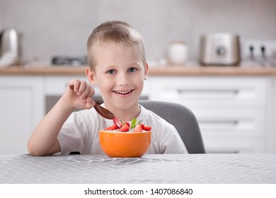 Little caucasian smiling boy sitting at the kitchen table and eat porridge with strawberry. Healthy breakfast before school and kindergarten at home.