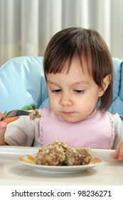 Little Caucasian toddler eats at the table on a light background