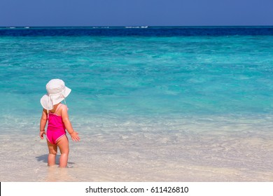 Little caucasian white girl one years old in a white mothers hat and pink swimsuit looking away having fun at exotic white sandy beach during vacation over the  turquoise sea and blue sky, copy space