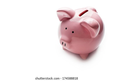 Little ceramic pink piggy bank or moneybox on a white background conceptual of saving money, finances, investment, security and goals