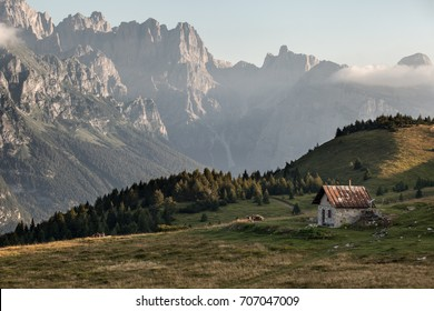 Little chalet with alps in the background