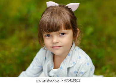 Little charming girl with brown eyes on the background of the forest in the summer seriously looking, close-up