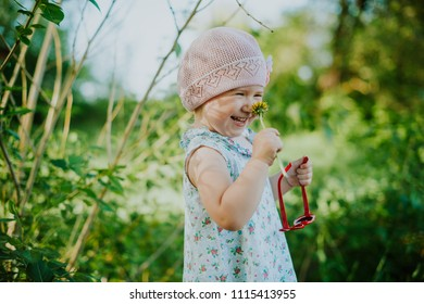 Little charming girl holding a flower and sunglasses on a beautiful green background in the park