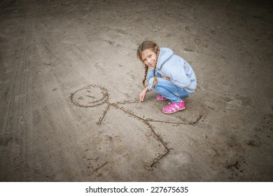 Little cheerful beautiful girl in sweater in sand draws funny man.