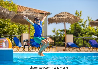Little cheerful boy jumping to the pool and making water splash, enjoying time in the refreshing water, having fun on the beach resort