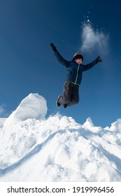 Little cheerful boy in sportswear jumps from a white snowy mountain against a blue sky.