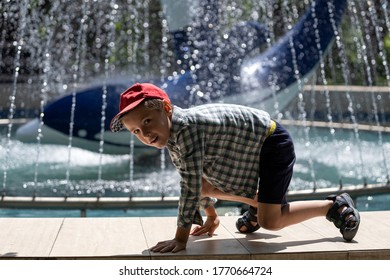 Little cheerful boy in summer shorts and a shirt plays and crawls like a monkey against the background of a summer green park and a fountain