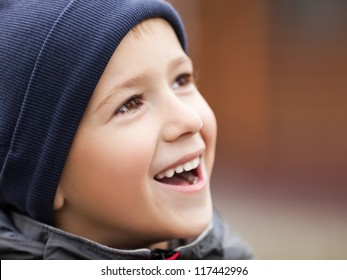 Little cheerful child boy walking outdoor and smiling for happiness and fun