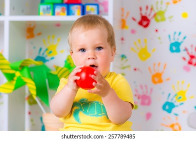 little cheerful child plays with a ball in the nursery