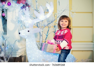 A little cheerful girl with a gift in her hands sits on a deer