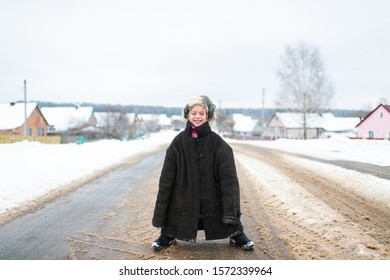 Little cheerful girl in oversized padded jacket standing on snowy road in winter day.