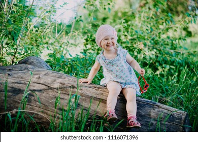 Little cheerful girl sitting on an old log on a background of a green forest