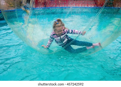 The little cheerful girl swims in a sphere on water