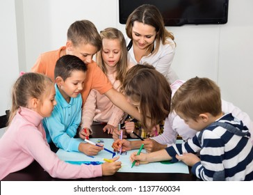 Little cheerful glad smiling children with teacher drawing together in classroom