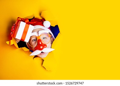 little cheerful Santa in glasses with a red nose and mustache gives a gift, getting out of the ragged yellow background