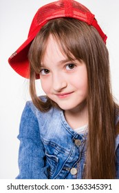 Little cheerful smiling girl in jeans suit and red cap