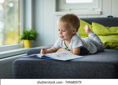 Little, cheerful, three years old boy lying on his belly on the sofa, with open book in front of him and shows something in that book.