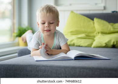 Little, cheerful, three years old boy lying on his belly on the sofa, with open book in front of him and turns the pages.
