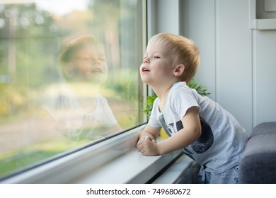 Little, cheerful three years old boy looking out  the window and thinking and waiting for something.