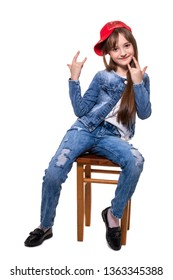 Little cheerful and very mobile girl in jeans suit and red cap posing sitting on a stool. Isolation on a white background