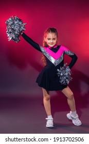 Little cheerleader practicing dance elements in studio with color light