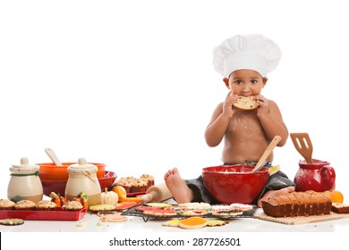 Little Chef.  Adorable biracial baby wearing a chef's hat and surrounded by baked goods.  Isolated on white with room for your text.