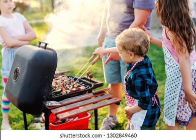 Little chef with apron grilling meat and vegetables on sticks. Next to him his cousins. Family gathering concept.