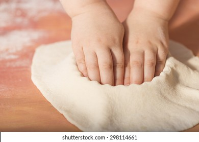 Little chef hands smeary with flour, putting the dough in the baking tray