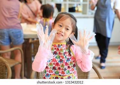 Little Chef wearing transparent plastic gloves in hands while cooking in the kitchen.