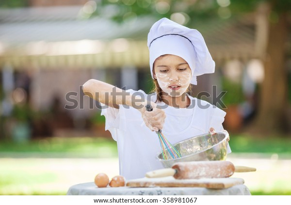 Little chef whipping eggs in a bowl outdoors