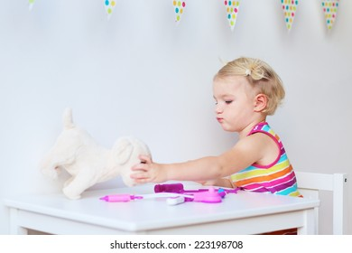 Little child, adorable blonde toddler girl, playing doctor role game and treating her puppy using different medical tools sitting at small white table in playroom at home, school or kindergarten