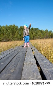 Little child with arm up and narrowing eyes standing on background on wooden planks pathway, swamp land