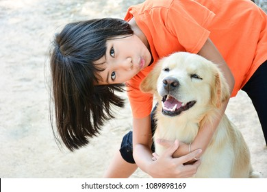 little child asian girl hug her dog , she kiss a dog and a dog smile , cocept of  friendship.