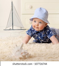 little child baby boy lying on the floor carpet indoors in baby room smiling hat clothing fashion