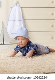 little child baby boy lying on the floor carpet indoors in baby room hat fashion clothing