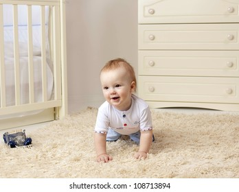 little child baby boy sitting on the floor on the carpet indoors in baby room smiling