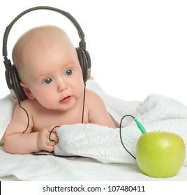 little child baby closeup portrait isolated on white studio shot face listening music headphones apple fruit