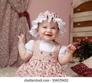 little child baby girl sitting indoors babyroom dress hat smiling happy