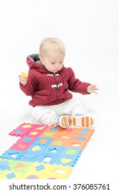 little child baby playing with puzzles warm clothing isolated on white studio shot
