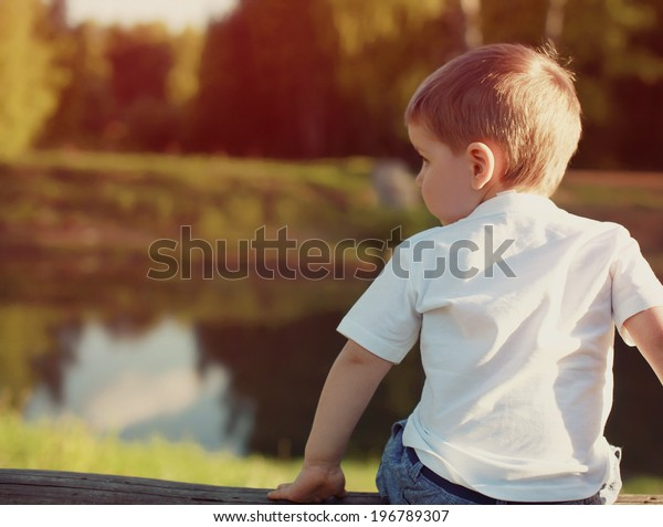 Little child from the back pensive looking away outdoors