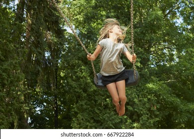 Little child blond girl having fun on a swing outdoor. Summer playground. Girl swinging high. Young child on swing outdoors