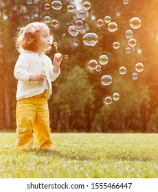 Little child blows bubbles in the sunset