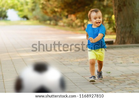 078cfa2e0345 Little child in blue shirt and yellow shorts running along paved road in  park and kicking